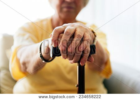 Senior woman holding a walking stick