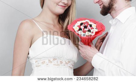Closeup Of Loving Couple With Candy Bunch Bouquet Flowers. Man And Woman Holding Present Gift. Relat