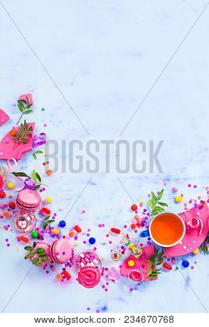 Colorful Celebration Flat Lay With Party Supplies, Confetti And Sweets. Pink Macarons With Tea Cup A