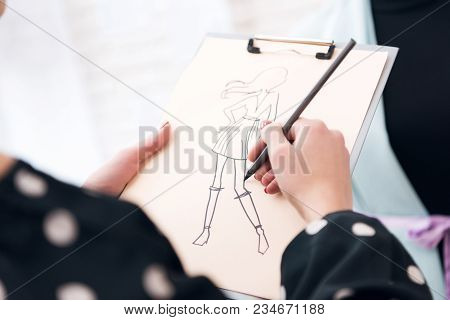 Close Up Woman At Garment Factory Making Sketch With Design For New Fashionable Dress.