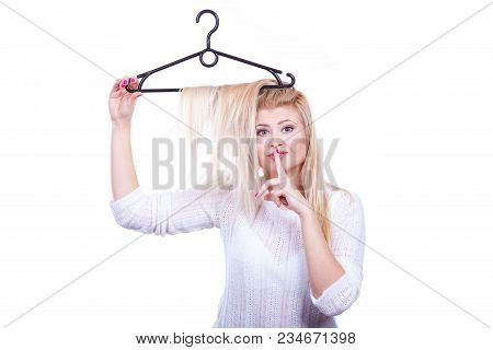 Hairstyle And Haircare Concept. Blonde Woman With Hair In Clothes Hanger Making Silence Gesture With