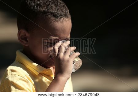 African American child drinking water outdoors. Water scarcity concept