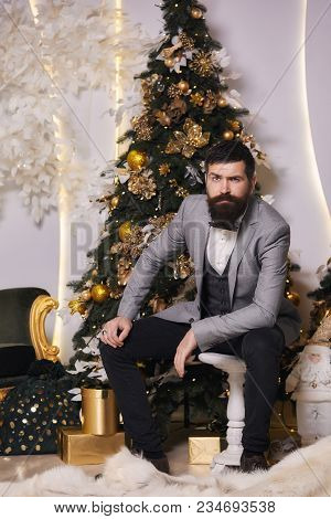 The Hipster Waiting For A Christmas Party. Pensive Man With A Beard In A Gray Jacket With A Bow-tie