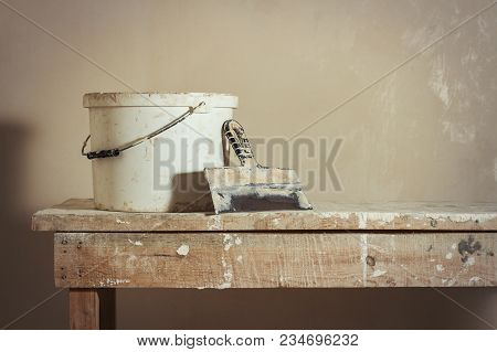 Scene of apartment repair. A bucket with putty and a putty knife on a wooden stand. poster