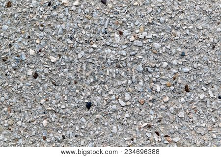 Concrete Wall With Decorative Coating Of Small Pebbles Of Different Sizes. The Surface Is Rough. Peb