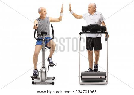 Seniors exercising on a stationary bike and a treadmill high-fiving each other isolated on white background