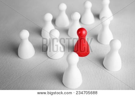 One red pawn among white ones on table. Difference and uniqueness concept