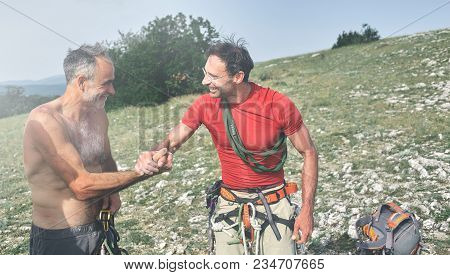Two Man Rock Climbers Climbed On The Cliff. Happy Climbers On The Top Of The Mountain. Friends Congr