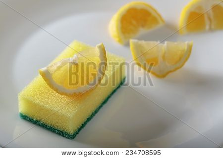 White Plate And Dish Sponge . Lemon Slices . Conceptual Image On The Theme Of Purity And Freshness .