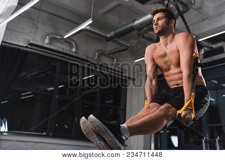 Handsome Shirtless Sportsman Exercising With Suspension Straps In Gym