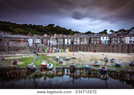 Many Boats Laying On Sand In Picturesque Fishing Village Harbour Of Mousehole Near Penzance, Cornwal