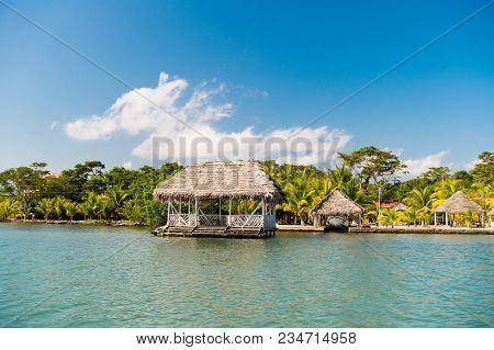 Huts On Sea Shore In Guatemala, Santo Tomas. Houses Of Wood And Grass On Tropical Beach On Sunny Blu