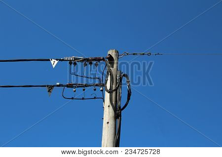 Concrete Electrical Power Line Utility Pole With Multiple Numbered Connected Wires On Clear Blue Sky