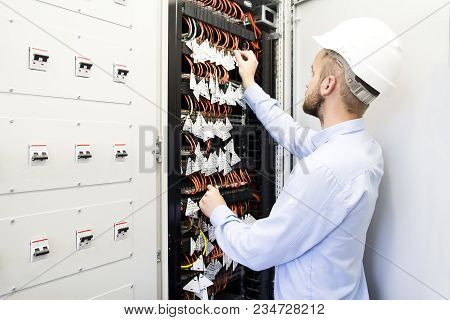 Service Engineer In Data Center. Worker In Helmet Near The Switches Of Optical Cables. Telecommunica