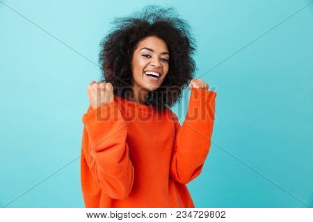 Colorful portrait of happy woman in red shirt looking on camera with smile and clenching fists like winner isolated over blue background