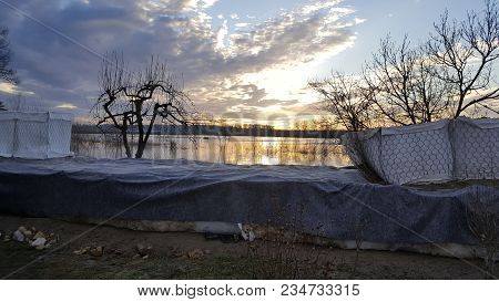 Sunrise On Cloudy Day Over Sandbox Barriers Flood Protection With Flooded Field, Trees, Branches And