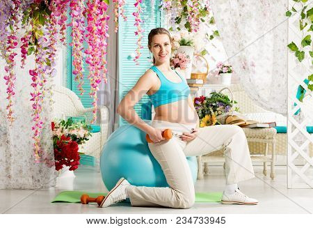 Pregnant Woman Doing Exercises With Gymnastic Fit Ball And Dumbbells In Summer Terrace With Flowers