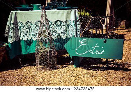 French Word Entree, Meaning Entrance, Written On Green Arrow Shape Board Outside Antique Shop