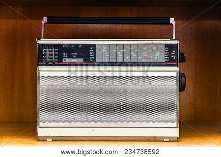 Old Vintage Dirty Analog Radio On Wooden Shelf