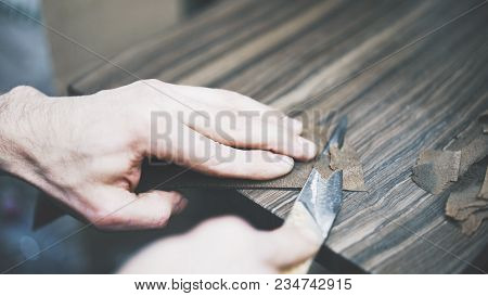 The Process Of Cutting A Leather In A Studio. A Man Cuts A Leather With A Knife. A Closeup Of Leathe