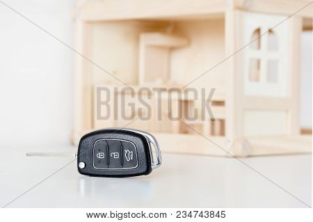 Car Keys With Wooden House Model On Background. Choice Of Byuing Basic Need. Decision Of Priority Or
