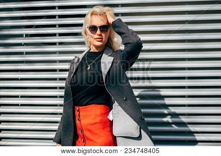 Fashion Girl In Fashionable Clothing. Beautiful Girl In A Coat And A Red Skirt. Posing In Street. Mo