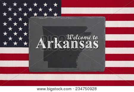 Welcome To Arkansas With State Map On A Black Chalkboard On A United States Of America Flag