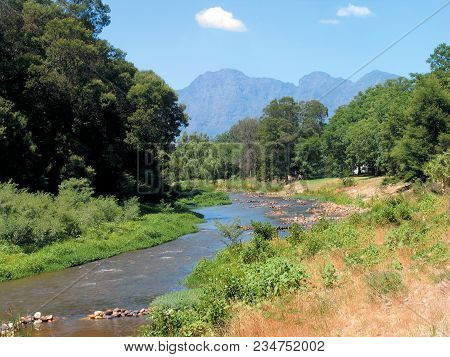 The Berg River, Surrounded By Trees And Other Vegetation, With A Mountain In The Back Ground