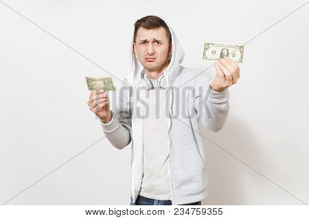 Young Handsome Shocked Male Student In T-shirt And Light Sweatshirt With Hood With Headphones Holds