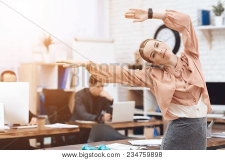 A Girl Is Doing Gymnastic Exercises At Work. She Works In A Business Office. She Is Tired.