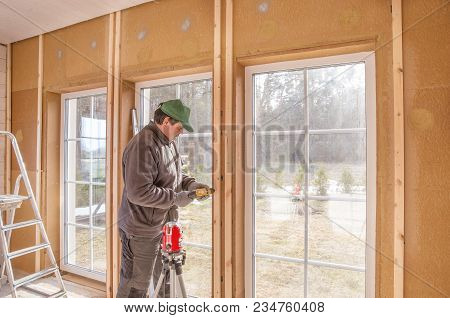 Construction Work, Finishing Work In A Wooden House And Installing Windows Using Laser Line Level