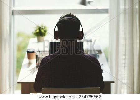 Rear View Of Freelancer In Headphones Working On Laptop
