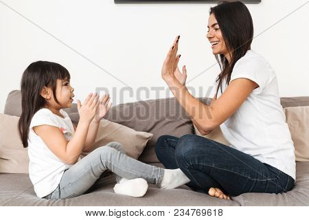 Portrait of cheerful family mother and girl playing together patty cake sitting on sofa in apartment