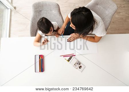 Image from above of young woman and little kid taking pleasure while sitting at table in flat and drawing picture with pencils