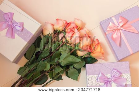 Gift Or Present Boxes And Flowers On Beige Background From Above