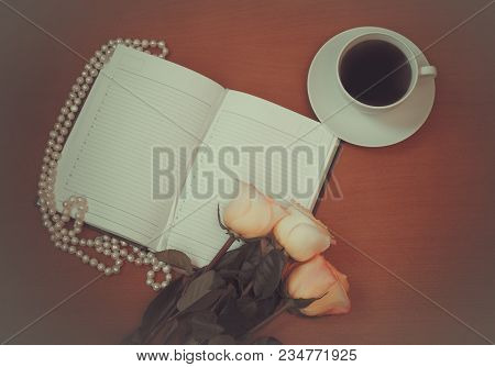 Diary, Pink Roses And Cup Of Coffee  On  Wooden Table. Top View With Gray Vignette. Vintage Style.