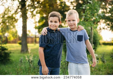 Two Children Are Playing In The Park. Two Beautiful Boys In T-shirts And Shorts Have Fun Smiling. Th
