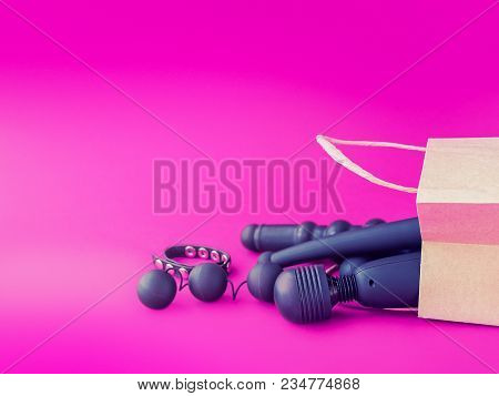 A Paper Shopping Bag Is Placed On A Background Of Fuchsia. Inside The Package Are Various Sex Toys.