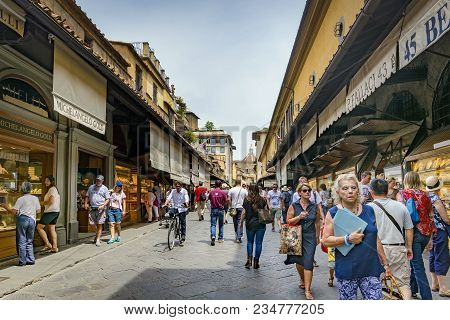Florence, Italy, June 2015: Tourists And Florentines Walking Along The Famous Ponte Vecchio With Its