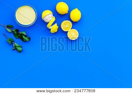 Lemon Curd In Bowl Among Lemons On Blue Background Top View.