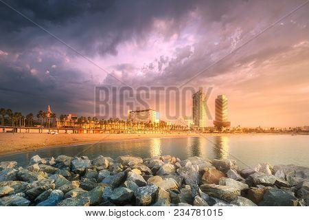 Barceloneta Beach In Barcelona With Rocky Coastline And Colorful Sky At Sunrise, Spain