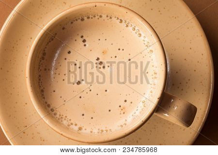 Cup Of Coffee Frothy Hot Drink On Beige Plate On Brown Background.