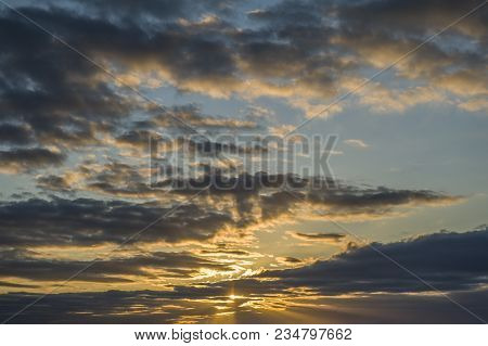Sun Setting In A Pale Blue And White Cloudy Sky