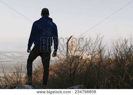 Adult Man (hiker) Standing On The Rock And Enjoying View With Blurred Castle On Background. Silhouet