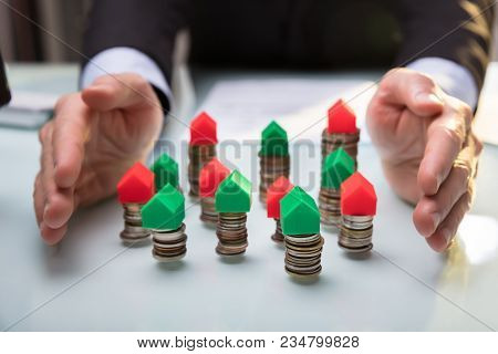 Businessperson Protecting House Models On Stacked Coins