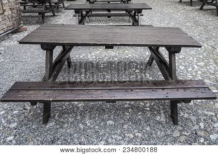 Focus On Wet Old And Awry Wood Tavern Style Table