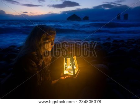 Night At The Beach, Blonde Woman With Lantern, Waves Of The Sea And Wild Rock Formations In The Back