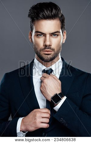 Close-up Handsome And Successful Man In An Expensive Suit. He Is In A White Shirt With A Tie. A Man
