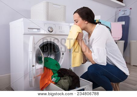Side View Of A Young Woman Smelling Cleaned Yellow Cloth Near Washing Machine