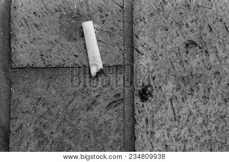 Discarded Burnt Cigarette On Ground Overhead View Black And Whtie